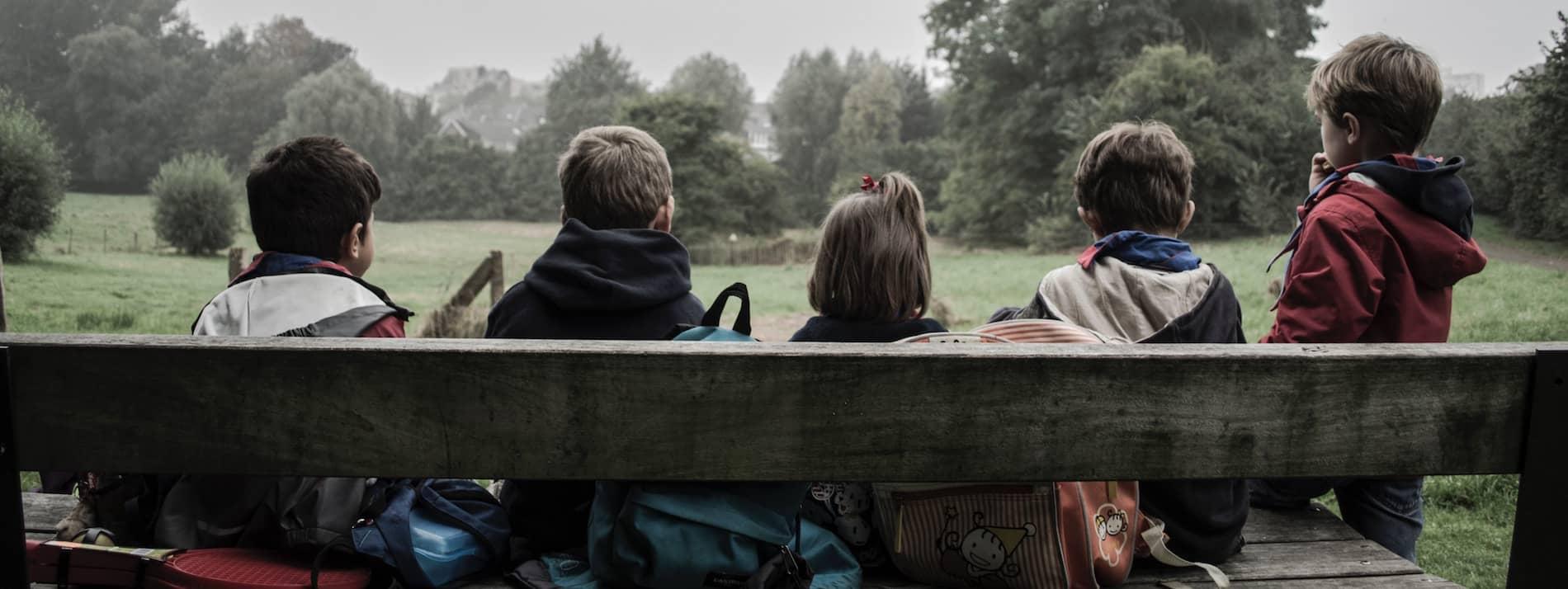 cinq enfants assis sur un banc